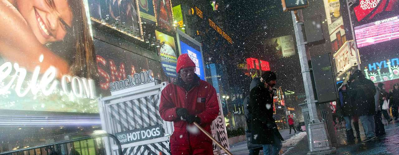 A sanitation worker squeegees snow and slush away in New York's Times Square, February 8, 2013. A blizzard blew into the northeastern United States on Friday, cutting short the workweek for millions who feared being stranded as state officials ordered roads closed ahead of what forecasters said could be record-setting snowfall. From New York to Maine, the storm began gently, dropping a light dusting of snow, but officials urged residents to stay home, rather than risk getting stuck in deep drifts when the storm kicks up later Friday afternoon. REUTERS/Keith Bedford (UNITED STATES - Tags: ENVIRONMENT)