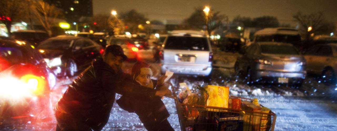 A child hangs on to shopping cart as his father pushes as they make their way to their car during a winter storm at Jersey City in New Jersey, February 8, 2013.A blizzard blew into the northeastern United States on Friday, cutting short the workweek for millions who feared being stranded as state officials ordered roads closed ahead of what forecasters said could be record-setting snowfall. From New York to Maine, the storm began gently, dropping a light dusting of snow, but officials urged residents to stay home, rather than risk getting stuck in deep drifts when the storm kicks up later Friday afternoon. REUTERS/Eduardo Munoz (UNITED STATES - Tags: ENVIRONMENT)