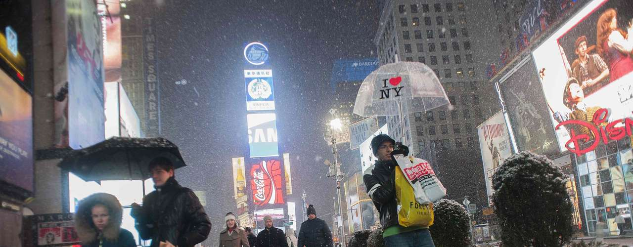 People make their way through snow in New York's Times Square, February 8, 2013.  A blizzard slammed into the northeastern United States on Friday, snarling traffic, disrupting thousands of flights and prompting five governors to declare states of emergency in the face of a fearsome snowstorm. REUTERS/Keith Bedford (UNITED STATES - Tags: ENVIRONMENT)