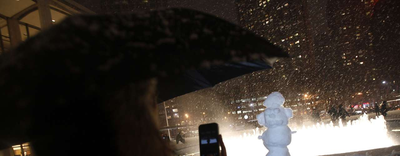 A woman takes a photo of a snow man that was erected at the fountain at Lincoln Center during New York Fashion Week in New York, February 8, 2013.  A blizzard blew into the northeastern United States on Friday, cutting short the workweek for millions who feared being stranded as state officials ordered roads closed ahead of what forecasters said could be record-setting snowfall. From New York to Maine, the storm began gently, dropping a light dusting of snow, but officials urged residents to stay home, rather than risk getting stuck in deep drifts when the storm kicks up later Friday afternoon.  REUTERS/Carlo Allegri  (UNITED STATES - Tags: ENVIRONMENT)