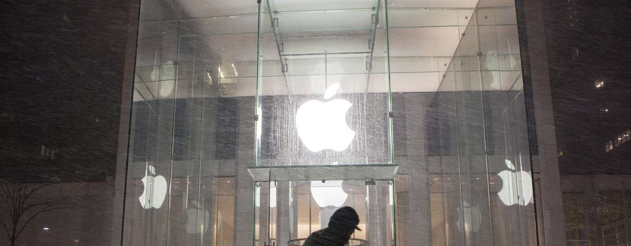 A man shovels snow in front of the Apple store in New York, February 8, 2013. A blizzard slammed into the north-eastern United States on Friday, snarling traffic, disrupting thousands of flights and prompting five governors to declare states of emergency in the face of a fearsome snowstorm.REUTERS/Keith Bedford (UNITED STATES - Tags: ENVIRONMENT)
