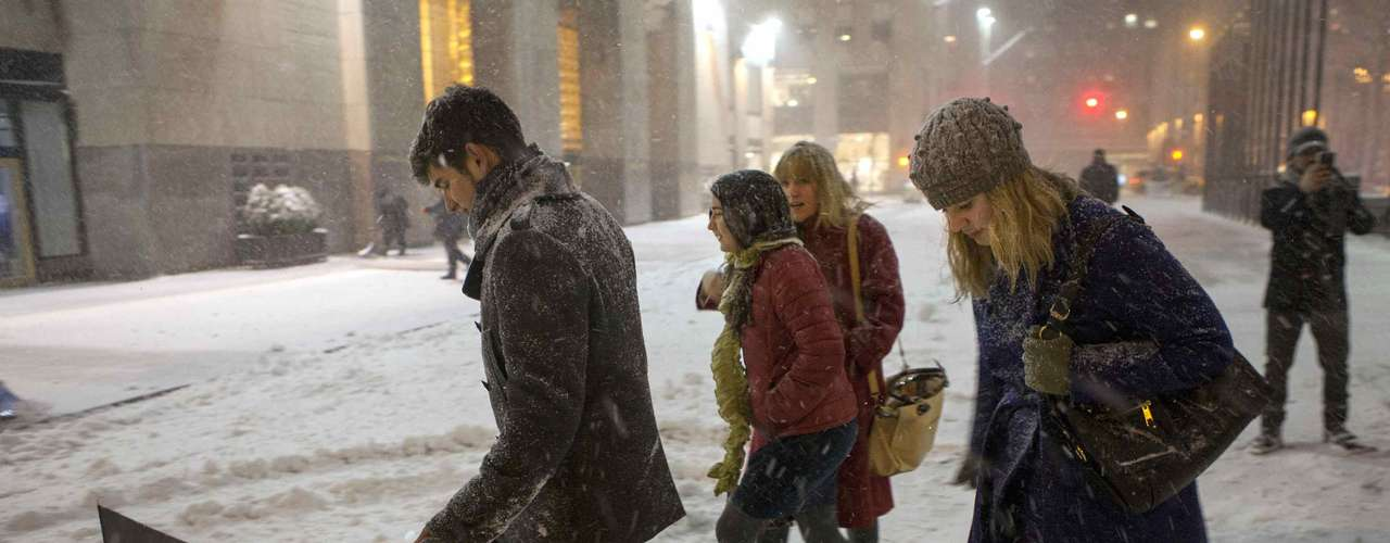 People make their way through snow in New York , February 9, 2013. A blizzard slammed into the north-eastern United States on Friday, snarling traffic, disrupting thousands of flights and prompting five governors to declare states of emergency in the face of a fearsome snowstorm.REUTERS/Keith Bedford (UNITED STATES - Tags: ENVIRONMENT)