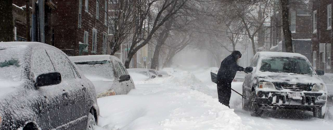 Hospital emergency room worker Susan Johnson shovels out her car to go to work during a severe winter storm in Boston, Massachusetts February 9, 2013. A blizzard pummelled the Northeastern United States, killing at least one person, leaving hundreds of thousands without power and disrupting thousands of flights, media and officials said.    REUTERS/Brian Snyder    (UNITED STATES - Tags: ENVIRONMENT DISASTER)