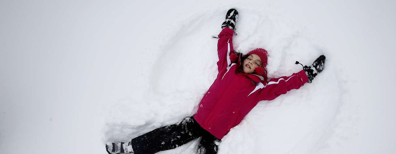 Phoebe Lightburn, 9, makes a snow angel in Central Park in New York February 9, 2013. A blizzard pummelled the Northeastern United States, killing at least one person, leaving hundreds of thousands without power and disrupting thousands of flights, media and officials said.   REUTERS/Carlo Allegri  (UNITED STATES - Tags: ENVIRONMENT SOCIETY)