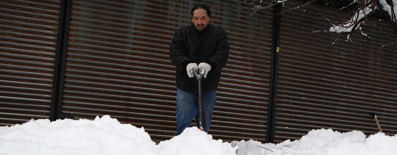A man shovels snow in the Brooklyn borough of New York, February 9, 2013. A blizzard pummeled the Northeastern United States, killing at least one person, leaving hundreds of thousands without power and disrupting thousands of flights, media and officials said. REUTERS/Eric Thayer (UNITED STATES - Tags: ENVIRONMENT)