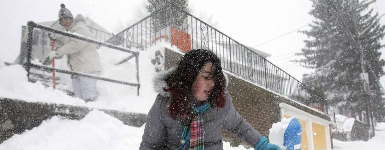 Caitlyn Morris (R) helps her grandmother Dottie Cayton (L) clear her sidewalk of snow during a blizzard in Medford, Massachusetts February 9, 2013. A blizzard pummelled the Northeastern United States, killing at least one person, leaving hundreds of thousands without power and disrupting thousands of flights, media and officials said.   REUTERS/Jessica Rinaldi (UNITED STATES - Tags: ENVIRONMENT)