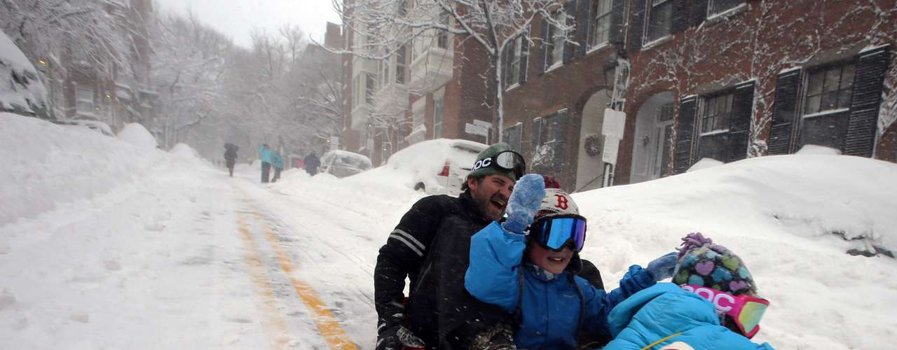 Peter Webster sleds down Chestnut Street with his children William (C) and Georgia (R) in Boston, Massachusetts February 9, 2013 during a winter blizzard.   REUTERS/Brian Snyder    (UNITED STATES - Tags: ENVIRONMENT)