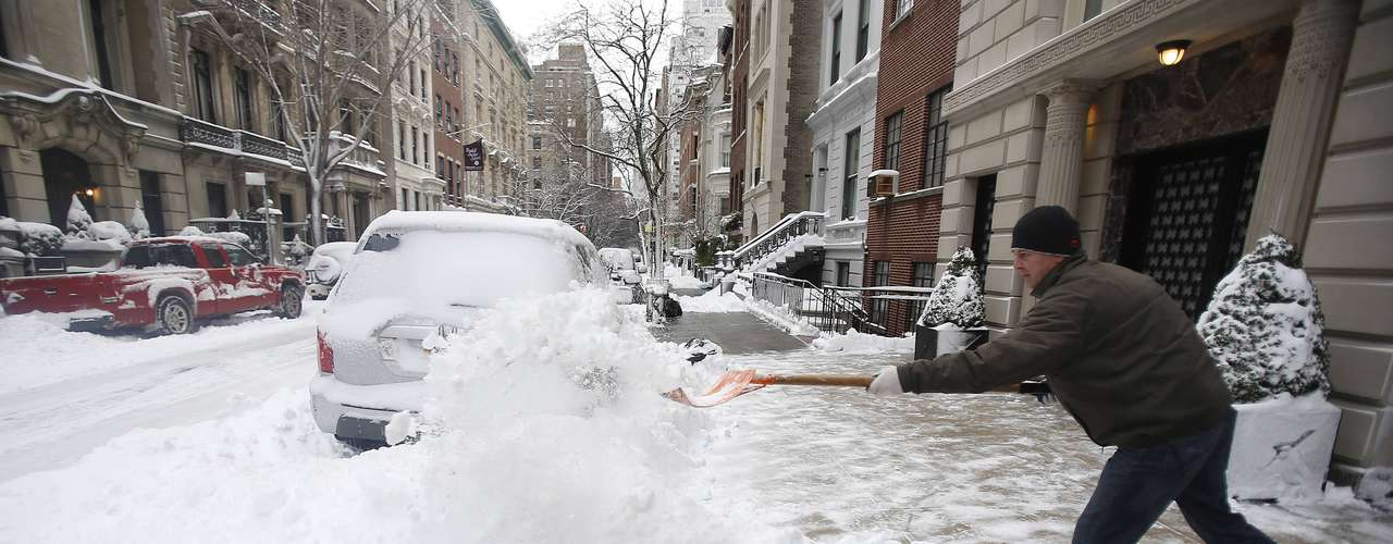 A man shovels snow from the sidewalk on the Upper East Side of New York February 9, 2013. A blizzard packing hurricane-force winds pummeled the northeastern United States on Saturday, killing at least one person, leaving about 600,000 customers without power and disrupting thousands of flights.  REUTERS/Carlo Allegri  (UNITED STATES - Tags: ENVIRONMENT)