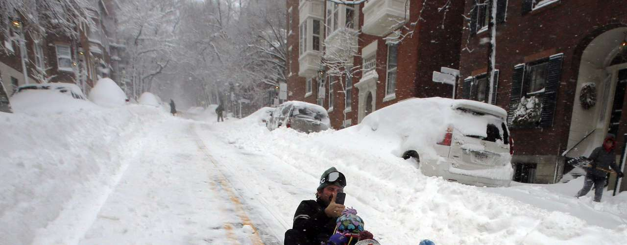 Peter Webster sleds down Chestnut Street with his children William (R) and Georgia (C) in Boston, Massachusetts February 9, 2013 during a winter blizzard.   REUTERS/Brian Snyder    (UNITED STATES - Tags: ENVIRONMENT)