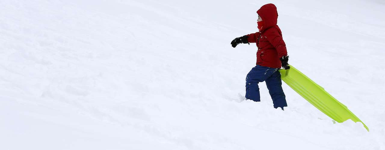 A child drags his toboggan up a hill in Central Park in New York, February 9, 2013. A blizzard pummelled the Northeastern United States, killing at least one person, leaving hundreds of thousands without power and disrupting thousands of flights, media and officials said.  REUTERS/Carlo Allegri  (UNITED STATES - Tags: ENVIRONMENT)