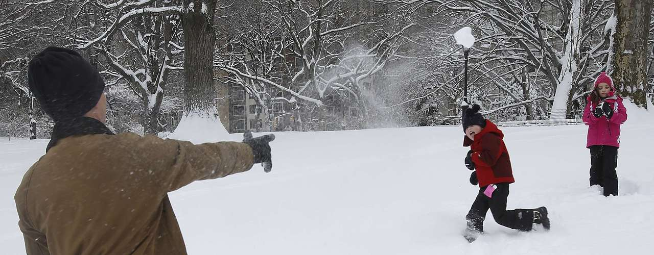 Richard Lightburn has a snowball fight with his children Phoebe, 9, and Carter, 6, in Central Park in New York, February 9, 2013. A blizzard pummelled the Northeastern United States, killing at least one person, leaving hundreds of thousands without power and disrupting thousands of flights, media and officials said.   REUTERS/Carlo Allegri  (UNITED STATES - Tags: ENVIRONMENT)