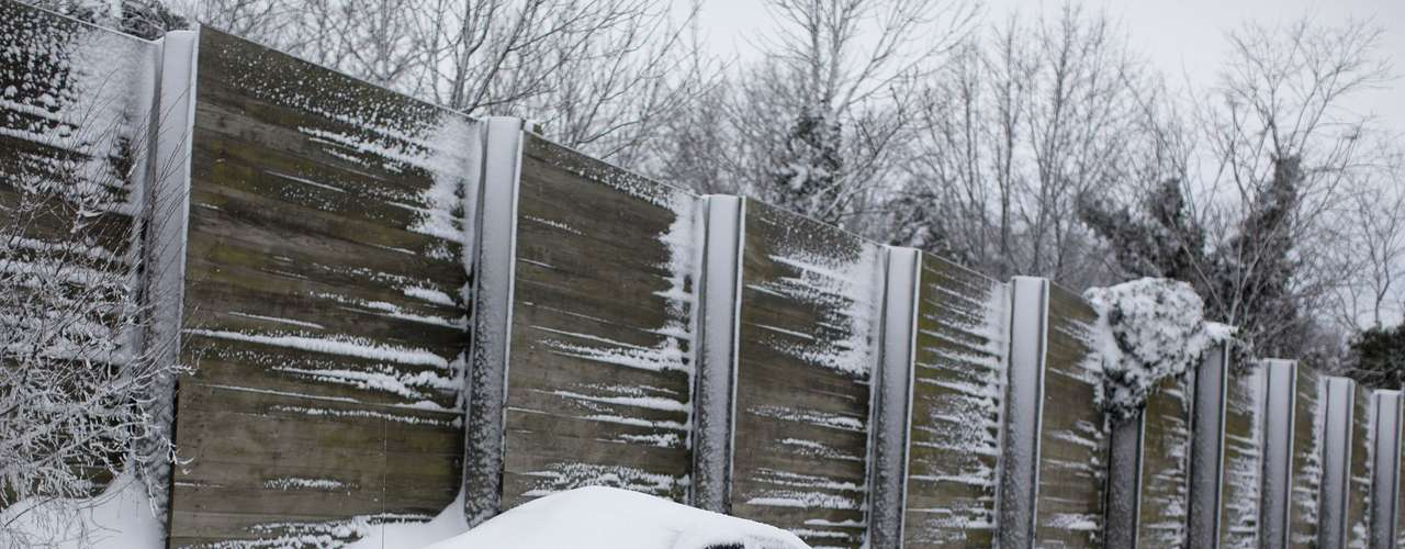 A car is seen buried in snow along the Long Island Expressway in the Suffolk County area of New York February 9, 2013. A blizzard packing hurricane-force winds pummeled the northeastern United States on Saturday, killing at least one person, leaving about 600,000 customers without power and disrupting thousands of flights. REUTERS/Shannon Stapleton (UNITED STATES - Tags: ENVIRONMENT DISASTER)