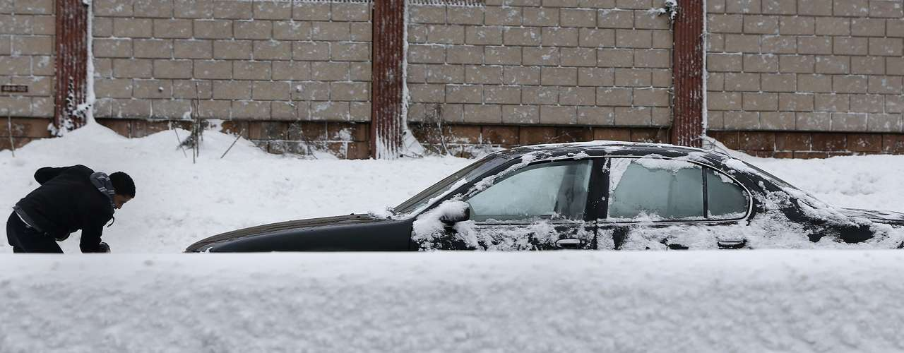 A man shovels snow from his car along the Long Island Expressway in the Suffolk County area of New York February 9, 2013. A blizzard packing hurricane-force winds pummelled the northeastern United States on Saturday, killing at least one person, leaving about 600,000 customers without power and disrupting thousands of flights. REUTERS/Shannon Stapleton (UNITED STATES - Tags: ENVIRONMENT DISASTER)