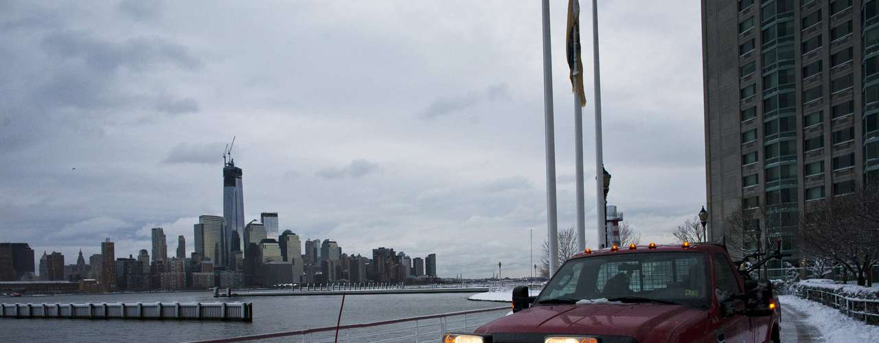 A truck with a snow plough cleans along the Hudson river as the skyline of New York's Lower Manhattan and One World Trade Center is seen at Newport in New Jersey, February 9, 2013. A blizzard pummelled the Northeastern United States, killing at least one person, leaving hundreds of thousands without power and disrupting thousands of flights, media and officials said. REUTERS/Eduardo Munoz (UNITED STATES - Tags: ENVIRONMENT DISASTER)