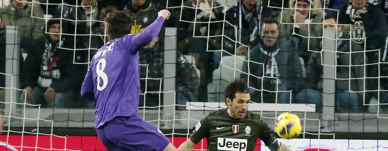 Juventus goalkeeper Gianluigi Buffon (R) makes a save against Stevan Jovetic.