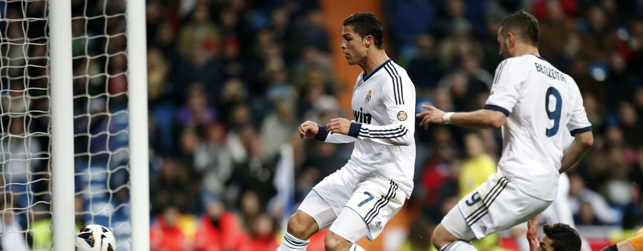 Cristiano Ronaldo (L) scores his third goal against Sevilla.