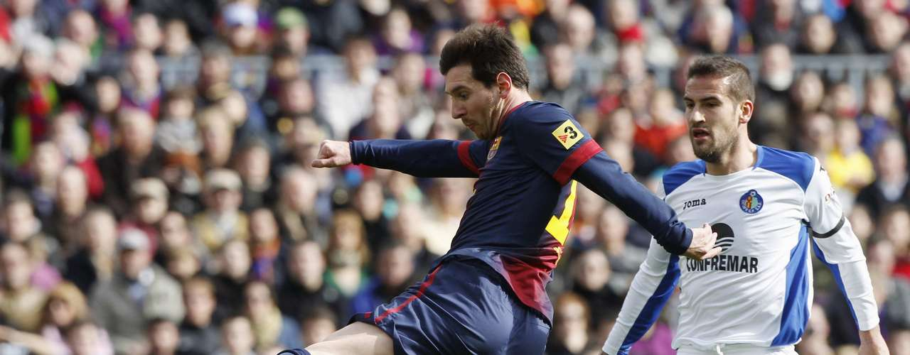 Barcelona's Lionel Messi shoots the ball next to Getafe's Lopo Garcia.