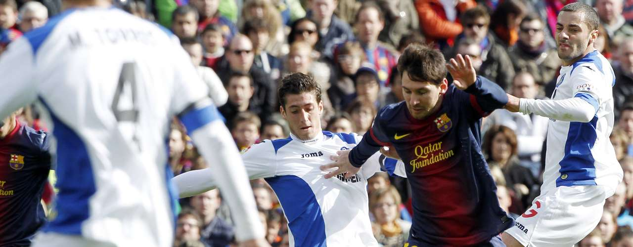 Barcelona's Lionel Messi (C) eludes Getafe's Miguel Torres (L), Sergio Escudero and Mehdi Lacen (R).