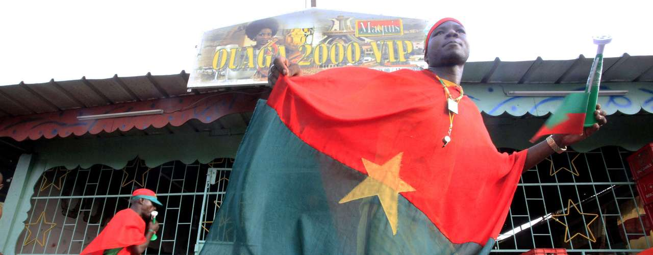 A Burkina Faso soccer fan living in Ivory Coast walks with a flag.