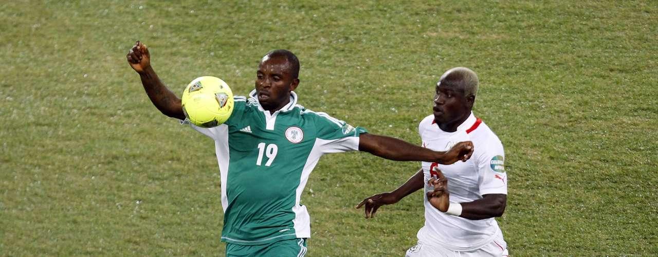 Burkina Faso's Djakaridja Kone (R) challenges Nigeria's Sunday Mbah.