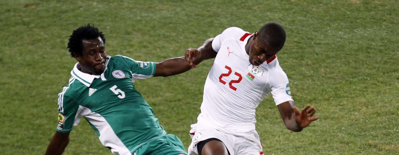 Burkina Faso's Prejuce Nakoulma fights for the ball with Nigeria's Efe Ambrose (L).