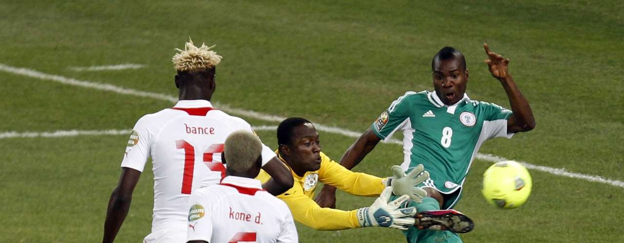 Burkina Faso's goalkeeper Daouda Diakite attempts to gather the ball as Nigeria's Brown Ideye (R) shoots.