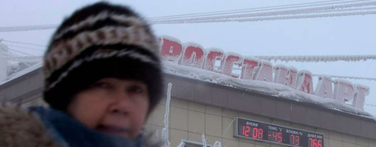 A woman passes a building, with the local time, temperature, humitiy and air pressure in Yakutsk.