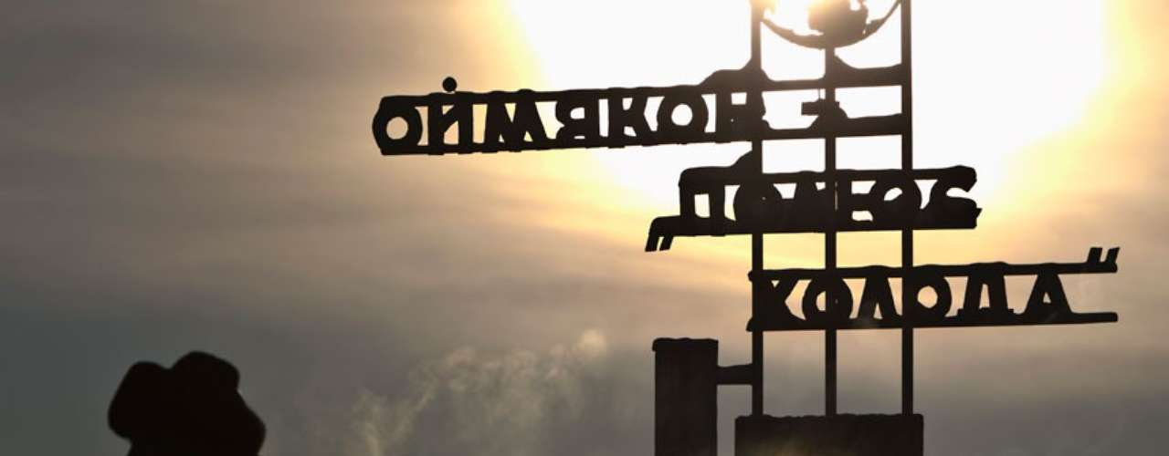A man passes through a sign for Omyakon Ice Polo, in the ancient site of the meteorological station.