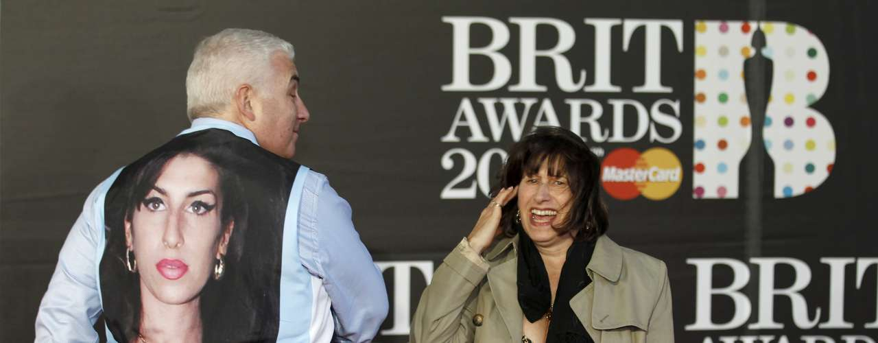 Mitch and Janis Winehouse, the father and mother of the late singer Amy Winehouse, laugh as they arrive for the BRIT Awards at the O2 Arena in London February 20, 2013. Mitch has taken off his jacket to display a picture of Amy on his waistcoat. Last month eyebrows were raised when Amy Winehouse was nominated in the British female solo category some 18 months after her death for a chart-topping album of unreleased songs and demos called \