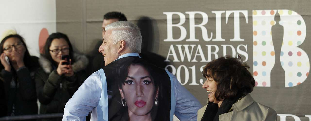 REFILE - REMOVING DISCLAIMER  Mitch and Janis Winehouse, the father and mother of the late singer Amy Winehouse, laugh as they arrive for the BRIT Awards at the O2 Arena in London February 20, 2013. Mitch has taken off his jacket to display a picture of Amy on his waistcoat. Last month eyebrows were raised when Amy Winehouse was nominated in the British female solo category some 18 months after her death for a chart-topping album of unreleased songs and demos called \