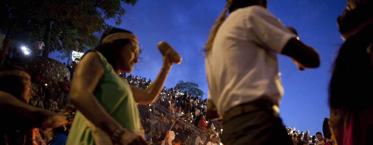 Un grupo de indígenas vestidos con sus coloridos atuendos tradicionales y adornos de plumas en sus cabezas bailaron alrededor de una fogata en la base de la escalera. Algunos soplaban una concha de caracol, en tanto, que otros sacudían maracas entre otros instrumentos musicales ancestrales al bailar alrededor de las llamas.