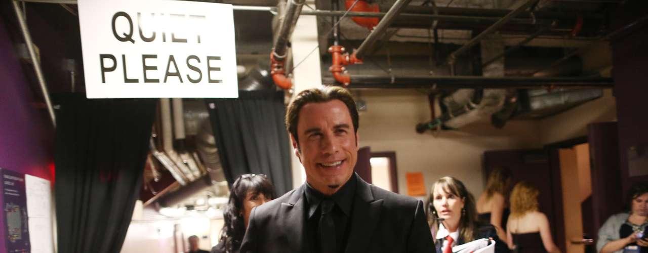 John Travolta sonríe mientras se prepara para subir al escenario y anunciar un número que rinde tributo a los mejores musicales de la última década.