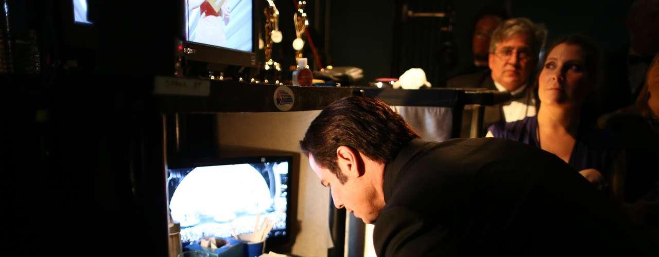 John Travolta, en el backstage, prepara cuidadosamente su presentación del premio de la Academia 2013 que le correspondió.