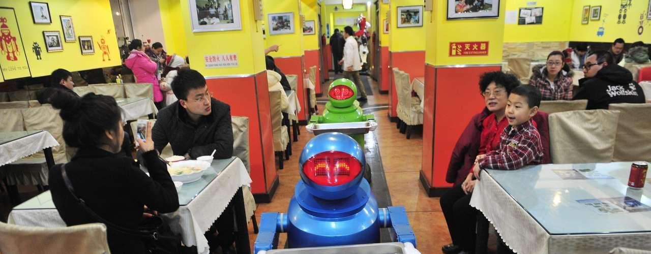 Un robot empuja una bandeja en un restaurante ambientado en el mundo de la robótica en un restaurante en Harbin, China. El restaurante abrió sus puertas en junio de 2012 y cuenta ahora con 20 robots que trabajan en cocina, como camareros e incluso dando la bienvenida a los clientes ya que algunos son capaces incluso de mantener una conversación básica con los clientes. Los robots varían de los 1,3 a los 1,6 metros y tienen una independencia de 10 horas sin recarga