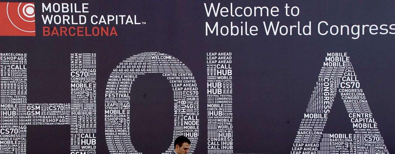 Un visitante posa ante el cartel que da la bienvenida al Mobile World Congress que se celebra en las nuevas instalaciones de la Fira de Barcelona.