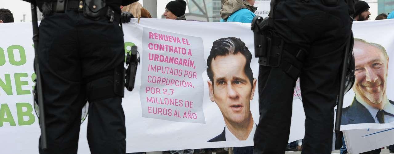 Policías españoles posan frente a un cartel que muestra a Inaki Urdangarin, yerno del Rey de España, acusado de corrupción. \