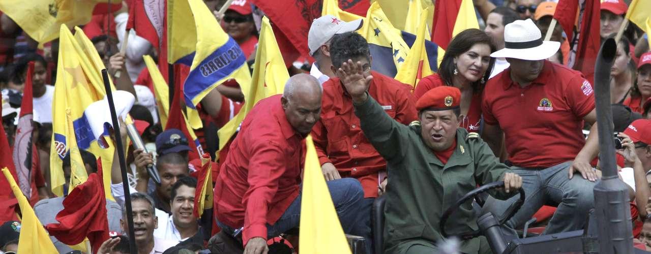En esta fotografía de archivo del 20 de febrero de 2010, se ve al presidente venezolano Hugo Chávez que maneja un camión mientras saluda a la multitud en una manifestación en conmemoración del 151er aniversario de la Guerra Federal en Caracas, Venezuela. El vicepresidente venezolano Nicolás Maduro anunció el martes 5 de marzo de 2013, que Chávez había muerto. (Foto AP/Ariana Cubillos, Archivo)