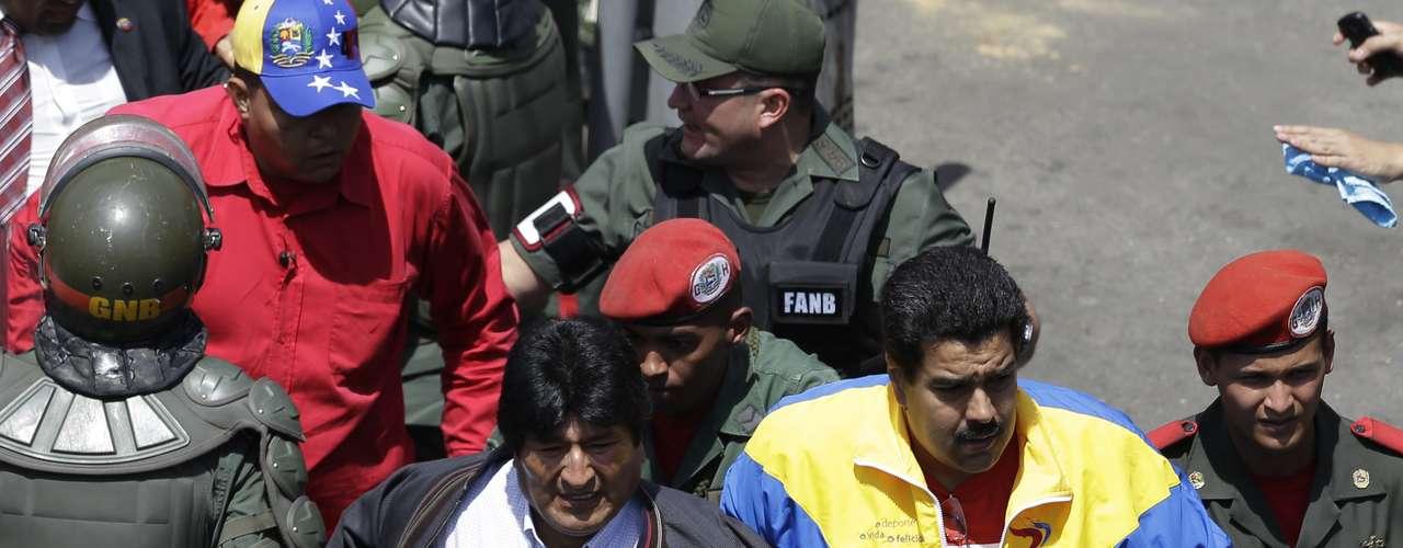 El vicepresidente venezolano Nicolás Maduro (der) toma del brazo al presidente boliviano Evo Morales cuando ambos se dirigen el 6 de marzo del 2013 al hospital de Caracas donde falleció Hugo Chávez. (AP Photo/Ricardo Mazalan)