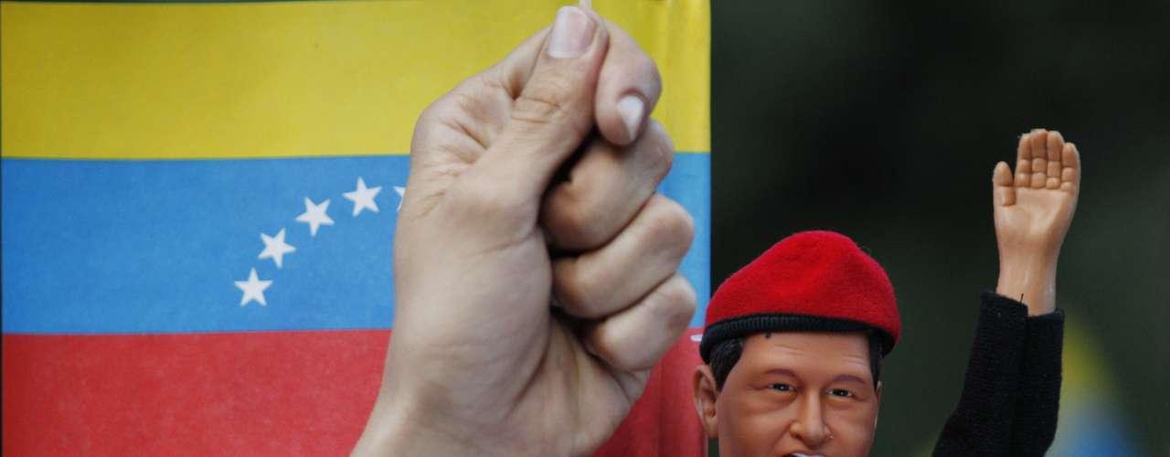 Un partidario del fallecido presidente venezolano Hugo Chávez carga un muñeco del mandatario durante una marcha en su honor en Bogotá, Colombia, el miércoles 6 de marzo de 2013. Chávez falleció a causa del cáncer a los 58 años el martes. (Foto AP/Fernando Vergara)