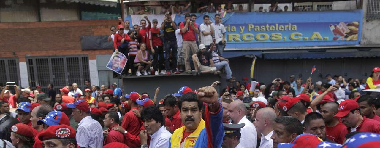 El vicepresidente de Venezuela Nicolás Maduro levanta su puño junto al presidente boliviano Evo Morales (centro) luego de acercarse al ataúd con los restos de Hugo Chávez el 6 de marzo del 2013 en Caracas. Maduro decretó siete días de luto por la muerte de Chávez, quien será enterrado el viernes 8 de marzo. (AP Photo/Rodrigo Abd)
