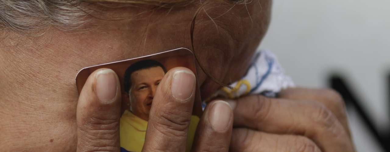 Una mujer sostiene una fotografía del fallecido presidente venezolano Hugo Chávez contra su rostro mientras llora fuera del hospital militar donde murió el jefe de Estado, el miércoles 6 de marzo de 2013 en Caracas, Venezuela. (AP foto/Ariana Cubillos)