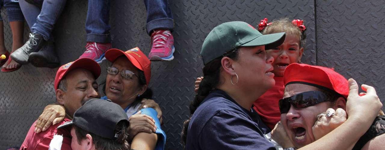 Simpatizantes del fallecido presidente de Venezuela Hugo Chávez lloran al paso del cortejo con los restos del mandatario en Caracas, Venezuela, el miércoles 6 de marzo de 2013.  (AP foto/Rodrigo Abd)
