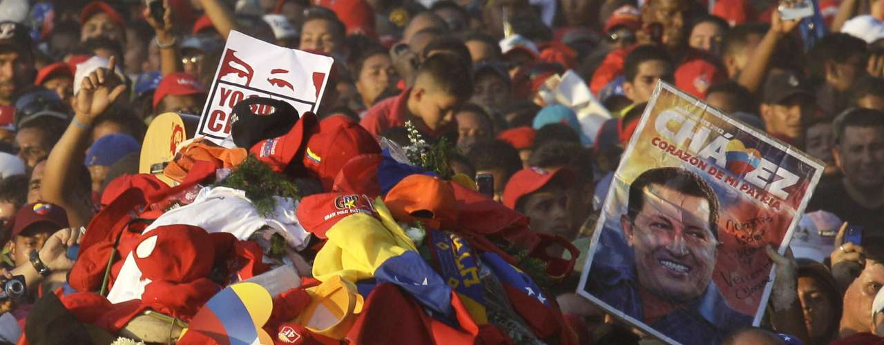 Cubierto de banderas, prendas y ofrendas que colocaron sus simpatizantes, el féretro del presidente venezolano Hugo Chávez es llevado a la Academia Militar en Caracas, el miércoles 6 de marzo de 2013  (AP Foto/Fernando Llano)