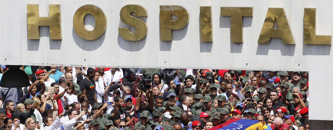 El vehículo con el ataúd que contiene los restos de Hugo Chávez, cubierto con una bandera de Venezuela, avanza entre una multitud al ser trasladado del hospital militar donde falleció el mandatario a una academia militar en la que permanecerá hasta el viernes, en que tendrá lugar el funeral. (AP Photo/Ariana Cubillos)