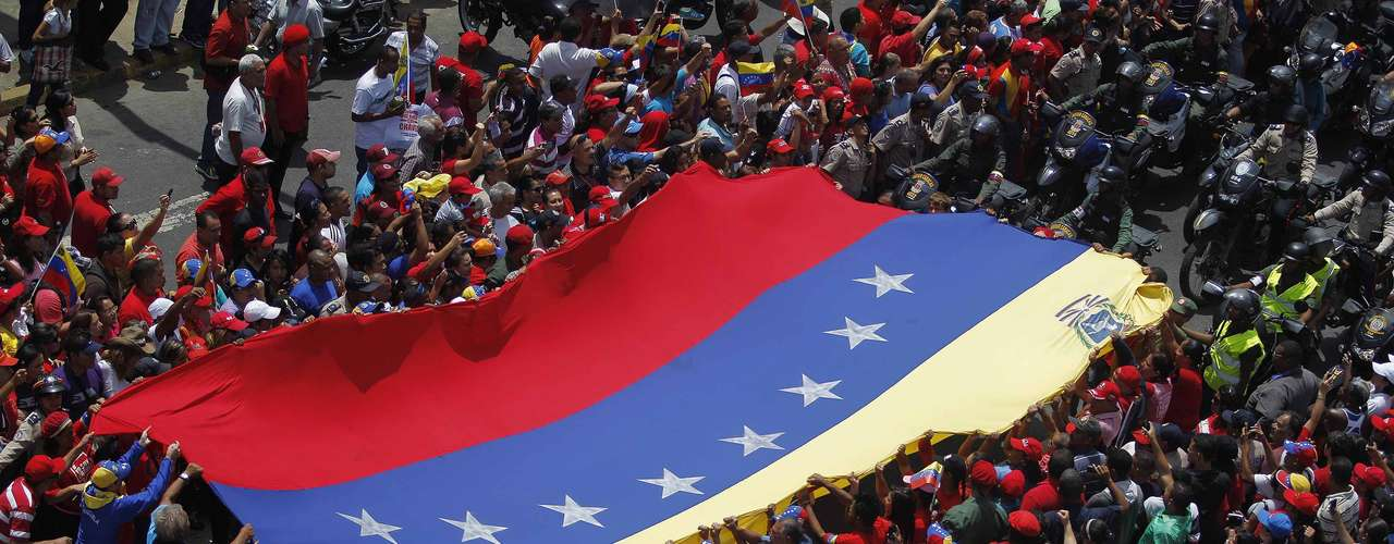 Supporters of Venezuela's late President Hugo Chavez stretch out a large national flag as they gather to see his coffin driven through the streets of Caracas, March 6, 2013. Chavez died on Tuesday of cancer, and authorities have not yet said where he will be buried after his state funeral on Friday.      REUTERS/Jorge Dan Lopez (VENEZUELA - Tags: POLITICS OBITUARY)