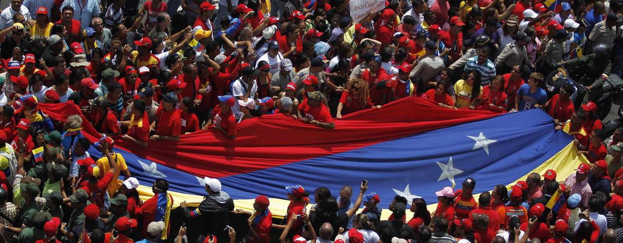 Supporters of Venezuela's late President Hugo Chavez unfurl a large national flag as they gather to see his coffin driven through the streets of Caracas, March 6, 2013. Chavez died on Tuesday of cancer, and authorities have not yet said where he will be buried after his state funeral on Friday.       REUTERS/Jorge Dan Lopez (VENEZUELA - Tags: POLITICS OBITUARY)