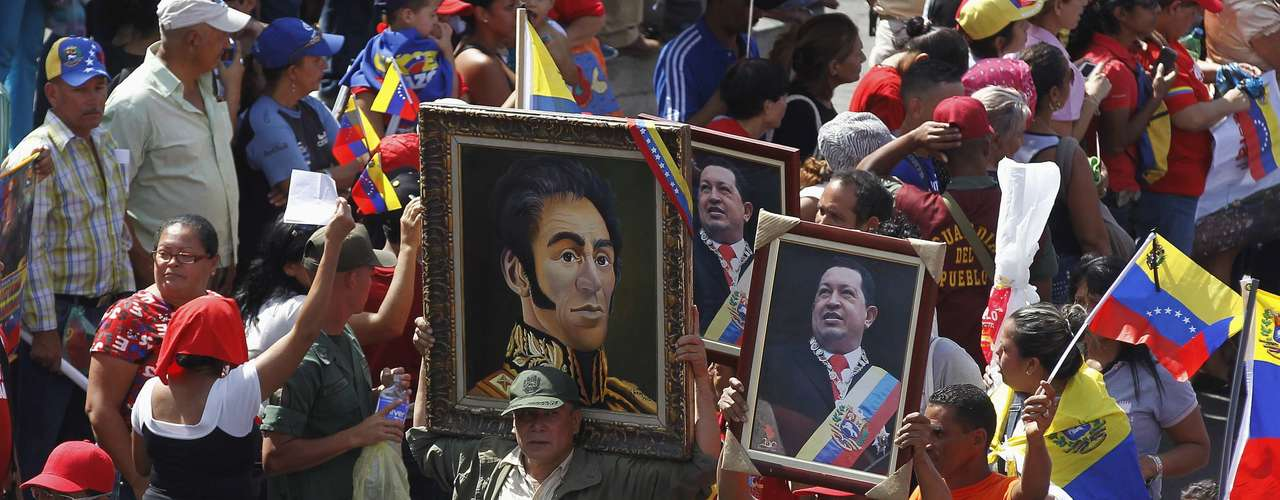 Supporters of Venezuela's late President Hugo Chavez carry portraits of him and independence hero Simon Bolivar as Chavez's coffin was driven through the streets of Caracas, March 6, 2013. Authorities have not yet said Chavez will be buried after his state funeral on Friday. REUTERS/Mariana Bazo (VENEZUELA - Tags: POLITICS OBITUARY)