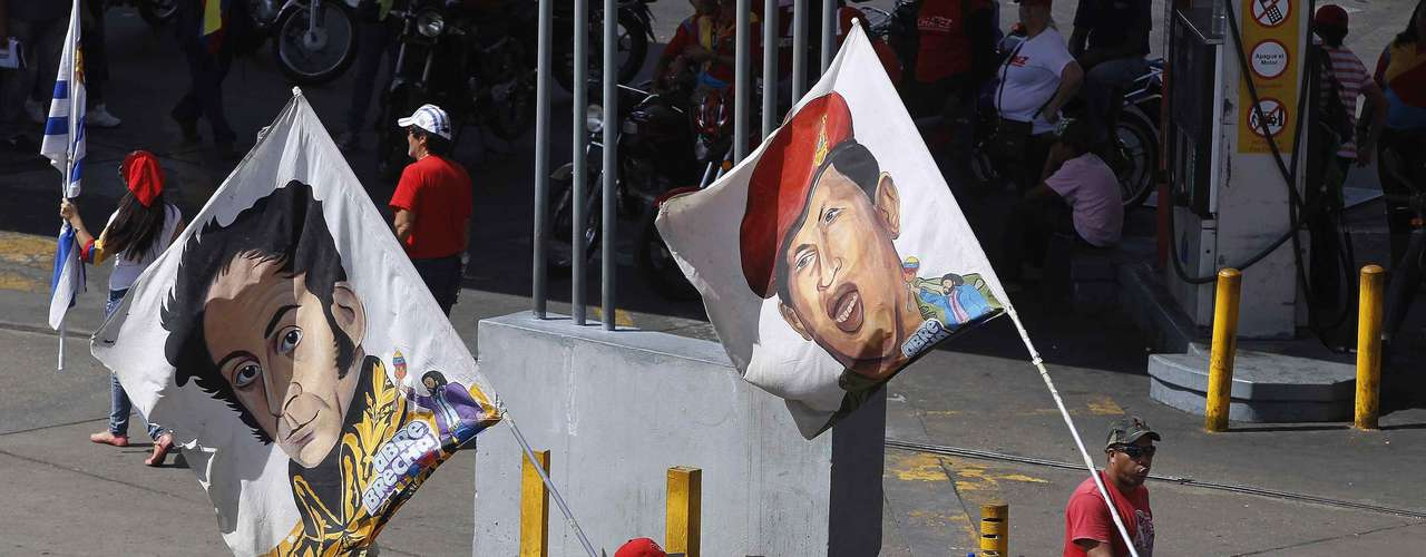 Supporters of Venezuela's late President Hugo Chavez carry flags with images of him and independence hero Simon Bolivar as Chavez's coffin was driven through the streets of Caracas, March 6, 2013. Authorities have not yet said where Chavez will be buried after his state funeral on Friday. REUTERS/Mariana Bazo (VENEZUELA  - Tags: POLITICS OBITUARY)