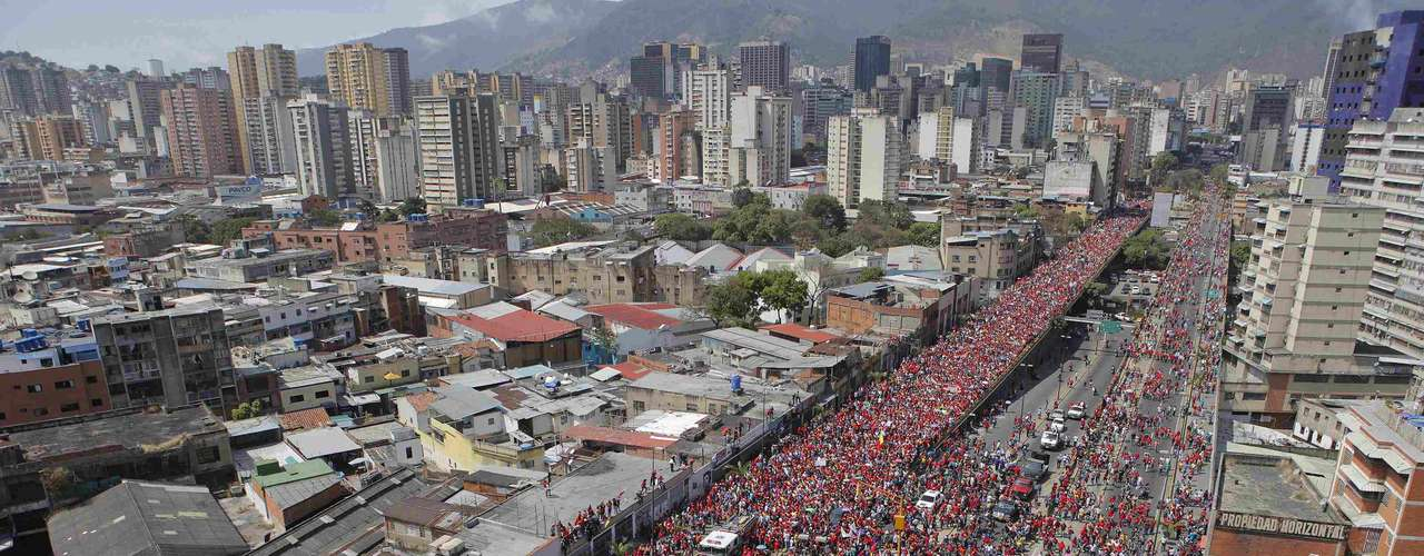 People follow the coffin of Venezuela's late President Hugo Chavez as it is driven through the streets of Caracas after leaving the military hospital where he died of cancer, in Caracas, March 6, 2013. Authorities have not yet said where Chavez will be buried after his state funeral on Friday. REUTERS/Marco Bello (VENEZUELA - Tags: POLITICS OBITUARY CITYSCAPE)