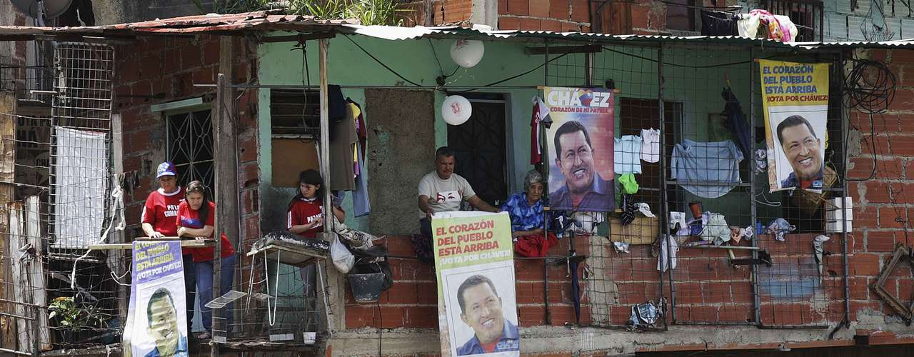 Supporters of Venezuela's late President Hugo Chavez hang portraits of him from their homes as his coffin was driven through the streets of Caracas, March 6, 2013. Authorities have not yet said where Chavez will be buried after his state funeral on Friday. REUTERS/Christian Veron (VENEZUELA - Tags: POLITICS OBITUARY SOCIETY)